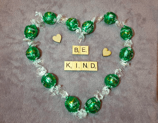 Heart outline created by Sweets with the Scrable Letters spelling Be kInd in the centre
