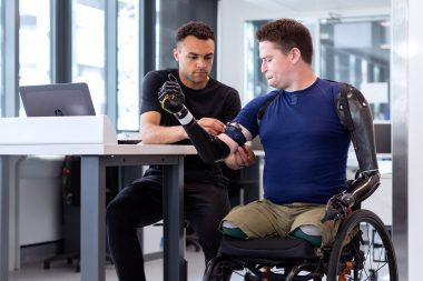 Young man in a wheelchair having a prosthetic arm fitted by a therapist also seated