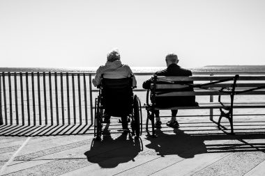 Person in a wheelchair next to a person seated on a bench looking out to sea