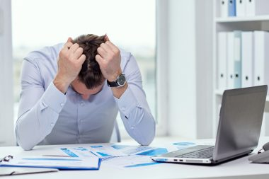 Man sat at an office desk with his head in his hands