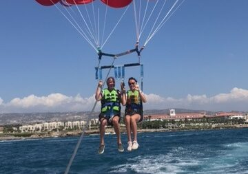 2 people parasailing with a red parachute above the sea on a sunny day